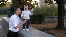 Father wakling with the baby. Baby boy walking in the park with daddy`s support stock video footage