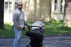 Father walk with baby carriage Royalty Free Stock Photo