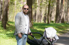 Father walk with baby carriage Royalty Free Stock Photos