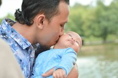 Asian father kisses baby on his arm with love near lake at outdoor park in day time stock photo