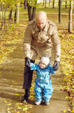 Father walking with baby son outdoors in autumn Stock Images