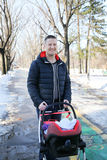 Father walking with baby stroller in city park Stock Photo