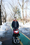 Father walking with baby stroller in city park Royalty Free Stock Photography