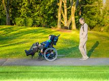 Father walking with disabled son in wheelchair at lake park royalty free stock photos