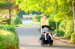 Father walking with disabled son in wheelchair at park Royalty Free Stock Image