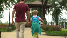 Father walking home with son after school, discussing sport classes, football. Stock footage stock video
