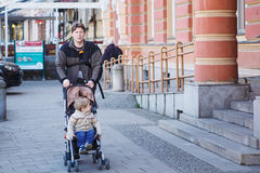 Father walking with little son in stroller in the city Stock Photo