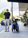 Father walking next to disabled son in wheelchair through town Stock Photography