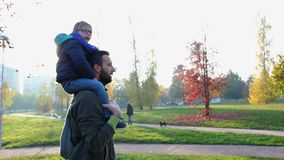 Father walking in urban city park with son on shoulders. Dad an child enjoy an autumn day outdoor together. Sunset. Backlit. Togetherness, family and childhood stock video