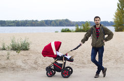 The father walks with his child in baby carriage in the park by Royalty Free Stock Images