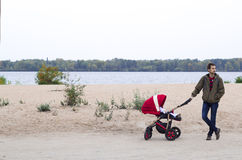 The father walks with his child in baby carriage in the park by Royalty Free Stock Image