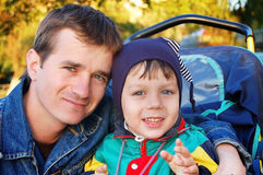 Father walks with young son sitting in a pram. In early fall. Sunset Stock Image