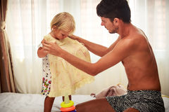 Father wants try on yellow dress to daughter at window Royalty Free Stock Photography
