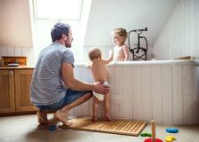 Father washing two toddlers in the bathroom at home. Father washing two toddlers in the bath in the bathroom at home. Paternity leave royalty free stock images