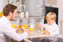 Father watches his son eating cornflakes Stock Photos