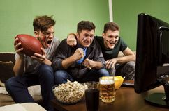Father watching American football match with children Royalty Free Stock Images
