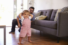 Father Watching Baby Daughter Take First Steps At Home Royalty Free Stock Image