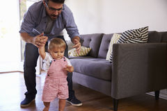 Father Watching Baby Daughter Take First Steps At Home Royalty Free Stock Photography