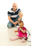 Father watching baby girl playing with cables Stock Image
