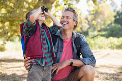 Father watching at boy looking through binoculars. Happy mature father watching at boy looking through binoculars Royalty Free Stock Images