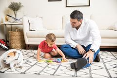 Father Watching Boy Playing With Toys By Dog At Home. Mid adult father watching boy playing with toys by dog in living room at home stock photo