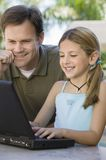 Father Watching Daughter Use Laptop Royalty Free Stock Photography