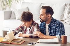 Father watching son doing homework concentrated sitting at table at home royalty free stock photo