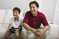 Father watching son play video game on couch Royalty Free Stock Image