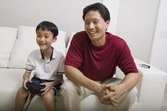 Father watching son play video game on couch front view Royalty Free Stock Images