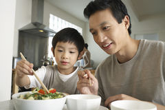 Father Watching Son Trying To Use Chopsticks. Young father watching son trying to use chopsticks at dining table stock photos