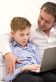 Father watching son working with laptop Stock Photography