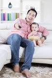 Father watching tv with daughter at home. Image of cheerful father watching tv with his daughter and sitting on the couch while eating popcorn at home Royalty Free Stock Images