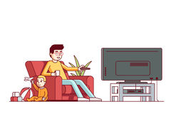 Father watching tv and looking after baby son. Father switching channels watching tv and looking after little baby son playing toys. Babysitter guy sitting with Royalty Free Stock Photography