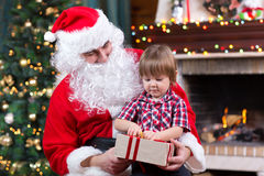 Father weared Santa Claus and kid boy open gift sitting near by Christmas tree at fireplace Stock Image