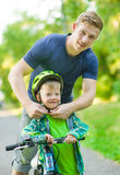 Father wears a bicycle helmet to his son Stock Photography