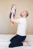 Father in white t-shirt and black jeans sitting on bed indoors, holding taking up newborn baby son. Portrait of middle age Caucasian father in white t-shirt and stock images