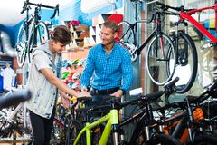 Father With Son Choosing Bike In Store Stock Photos