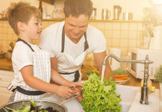 Father With Son Washes Vegetables Before Eating Royalty Free Stock Image
