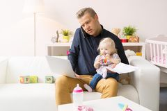 Busy father working with computer while looking after his baby girl Royalty Free Stock Photos