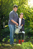 Father working at garden with cute little daughter Stock Images