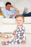 Father working at home while looking after child stock photo