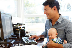 father working in home office with baby stock photography