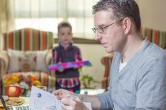 Father working in home office and son playing Stock Photos