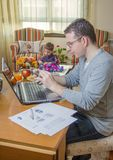 Father working in home office and son playing Stock Photography
