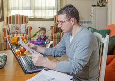 Father working in home office and son playing. Father reading business documents in home office and his boring son playing on the background royalty free stock photography