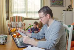 Father working in home office and son playing. Father reading business documents in home office and his boring son playing on the background stock photos