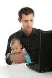 Father working on laptop while babysitting. Handsome young father with his daughter working on laptop Royalty Free Stock Photo