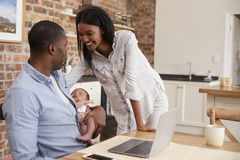 Father Working On Laptop Holds Newborn Son With Mother Stock Photography