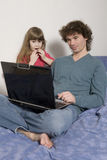 Father working on laptop from home. While babysitting his daughter Stock Photo