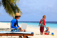 Father working on laptop while kids play at beach Stock Images